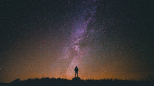Silhouette of a person against a starry night sky backdrop